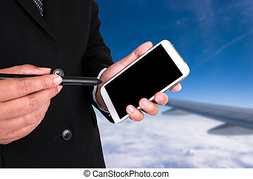 businessman's hands with a pocketpc, background with plane...