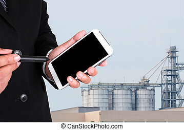 businessman's hands with a pocketpc, Blurry factory...