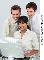 Businessmen and ethnic businesswoman working with a computer