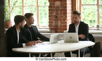 Businessmen discussing contract during negotiations sitting at conference office table