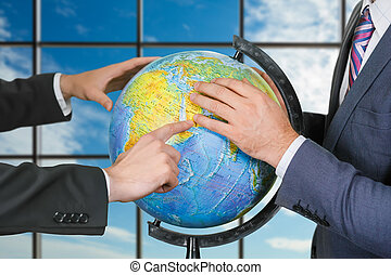 Men studying globe near window. - Businessmen explore globe...
