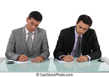 Businessmen filling in forms