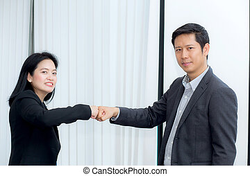 businessmen giving fist bump after business achievement in meeting room - teamwork concept.