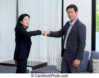 businessmen giving fist bump after business achievement in meeting room - teamwork concept.