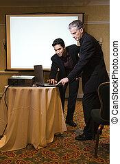 Businessmen giving presentation.
