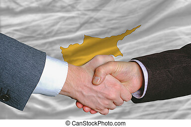 two businessmen shaking hands after good business investment agreement in cyprus, in front of flag