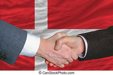 businessmen handshake after good deal in front of denmark...