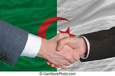 businessmen handshake after good deal in front of algeria flag