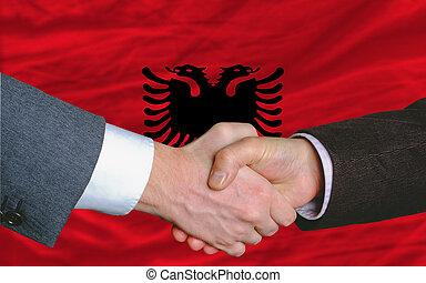 businessmen handshake after good deal in front of albania flag