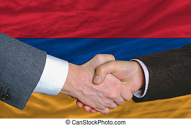 businessmen handshake after good deal in front of armenia flag