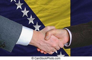 businessmen handshake after good deal in front of bosnia herzegovina flag