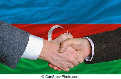businessmen handshake after good deal in front of azerbaijan flag