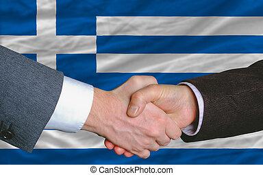 businessmen handshake after good deal in front of greece flag