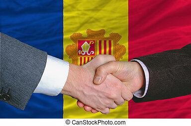 businessmen handshake after good deal in front of andora flag