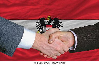businessmen handshake after good deal in front of austria flag