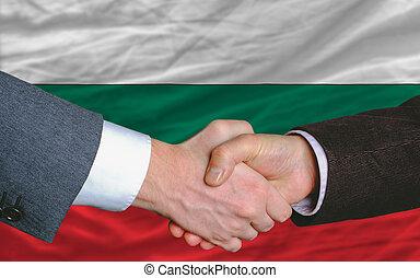 businessmen handshake after good deal in front of bulgaria flag