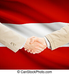 Businessmen handshake with flag on background - Austria