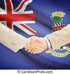 Businessmen handshake with flag on background - Cayman Islands