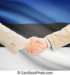 Businessmen handshake with flag on background - Estonia