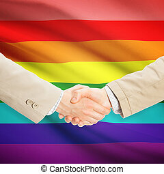 Businessmen handshake with flag on background - LGBT people