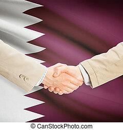 Businessmen handshake with flag on background - Qatar