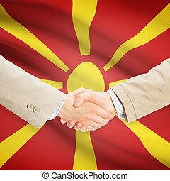 Businessmen handshake with flag on background - Republic of Macedonia
