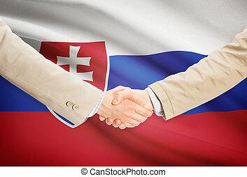 Businessmen handshake with flag on background - Slovakia