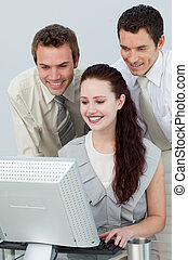 Businessmen helping a businesswoman with a computer