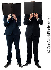 Businessmen hiding their faces with folder - Two businessmen...