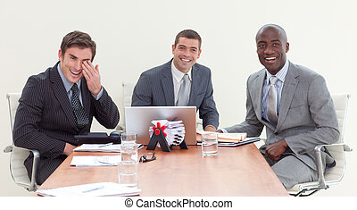 Happy businessmen sitting in a meeting smiling at the camera