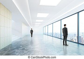 Businessmen in concrete corridor