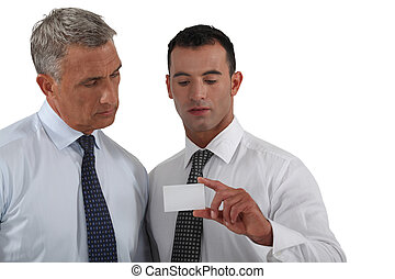 businessmen looking at a business card