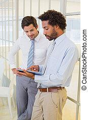 Businessmen looking at digital tablet in office