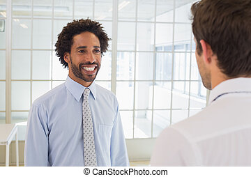 Businessmen looking at each other in office - Two smiling...
