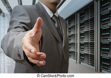 businessmen offer hand shake in a technology data center