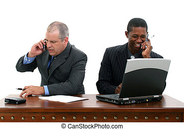 Businessmen on Cellphones at Desk - Two businessmen at desk...