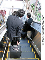 Businessmen on moving staircase - A group of three...