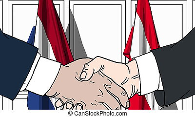 Businessmen or politicians shake hands against flags of ...