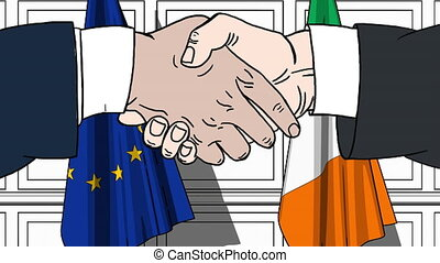 Businessmen or politicians shake hands against flags of the...