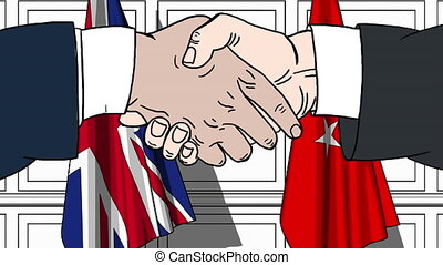 Businessmen or politicians shaking hands against flags of...