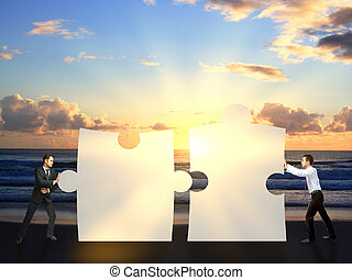 Businessmen pushing puzzle pieces together - Two businessmen...