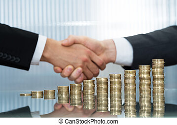 Businessmen Shaking Hand In Front Of Stacked Coins