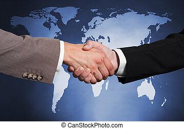 Businessmen Shaking Hands Against Worldmap - Cropped image...