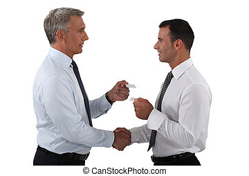 businessmen shaking hands and exchanging cards