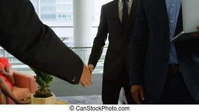 Businessmen shaking hands in office 4k