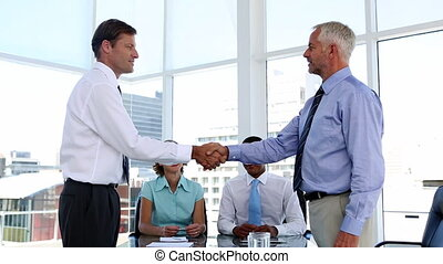 Businessmen shaking hands in the me