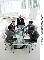 Businessmen shaking hands sitting around a conference table...