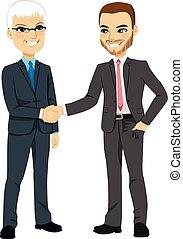 Businessmen Shaking Hands - Two businessmen, one senior and...
