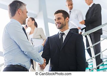 Businessmen shaking hands. Two confident businessmen shaking hands and smiling while standing at the staircase together with people in the background