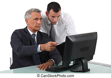 Businessmen sitting at a computer